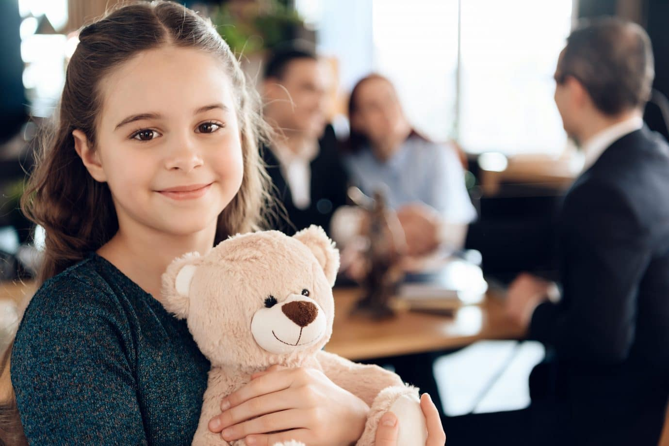 Happy little girl is hugging teddy bear at office of family lawyer. Registration of guardianship. Family in office of family lawyer