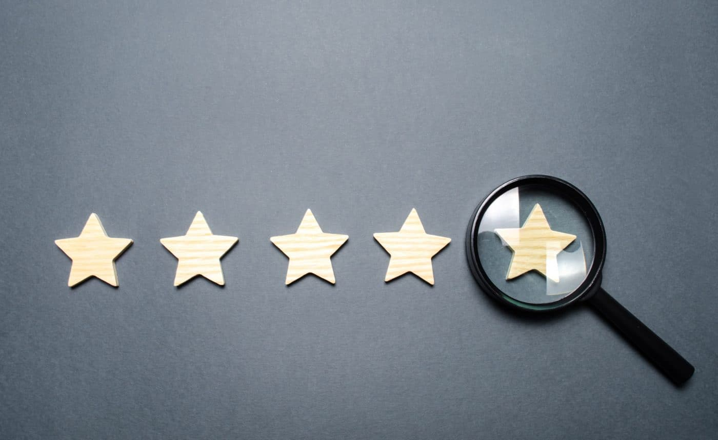 Five stars and a magnifying glass on the last star. Check the credibility of the rating or status.