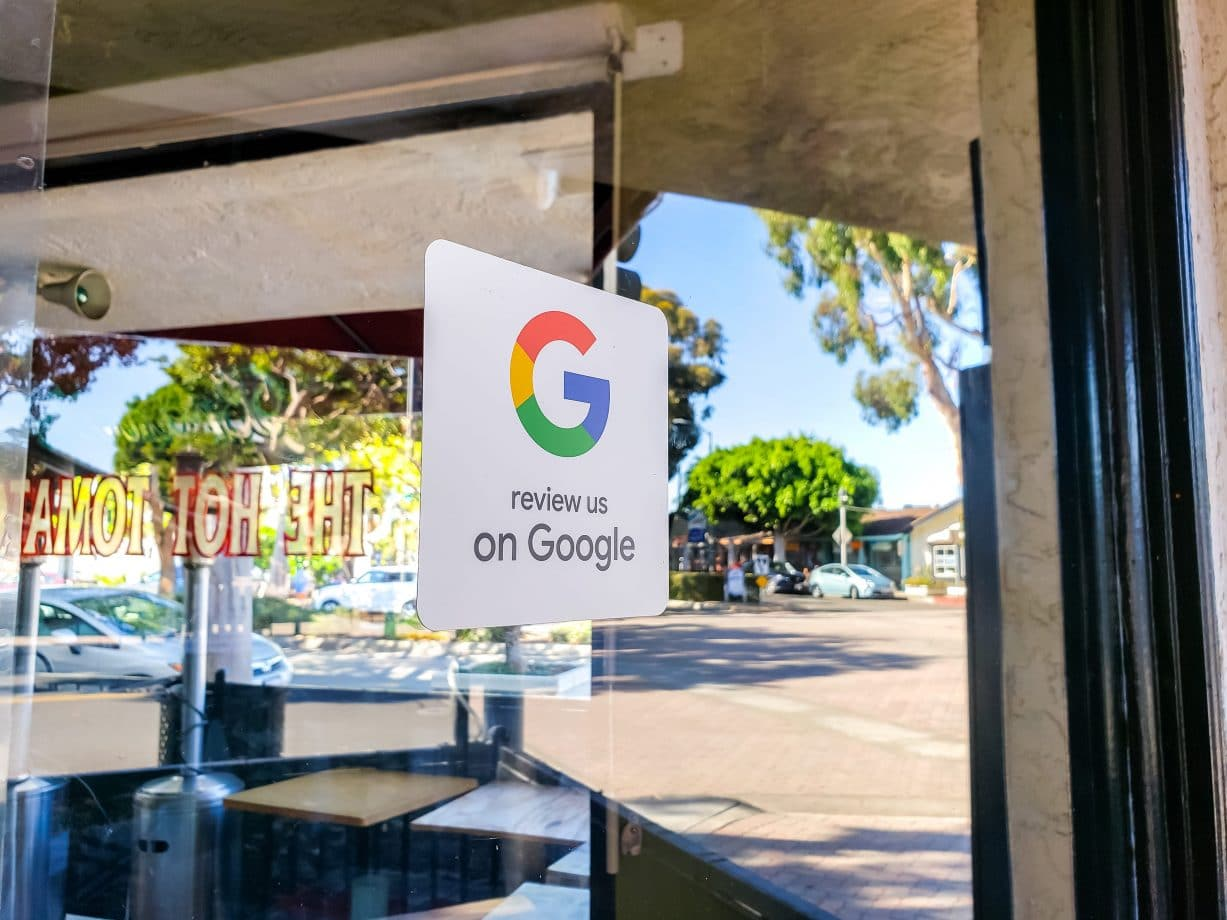 A retail store window sticker advertising to guests and customers to provide reviews on Google Maps
