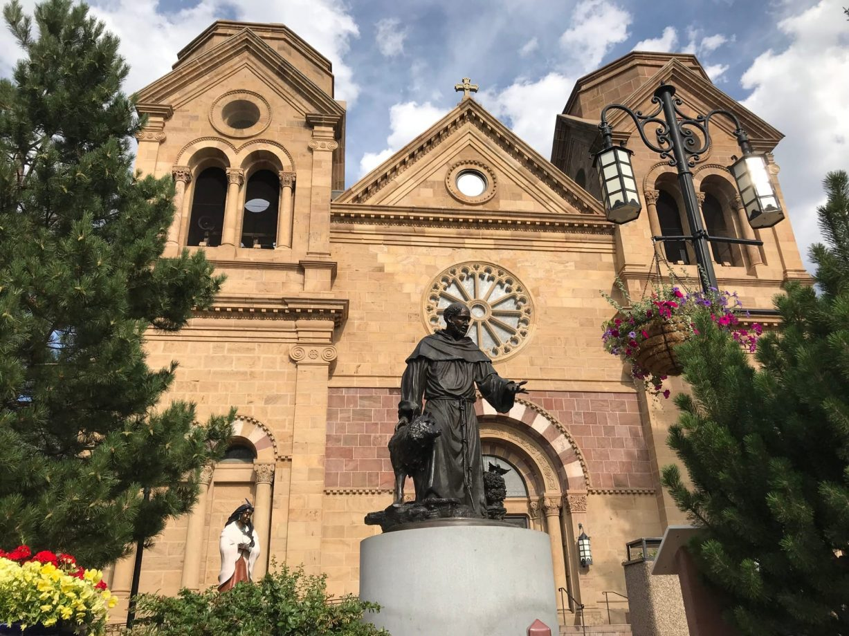 Statue in front and facade of the Cathedral Basilica of Saint Francis of Assisi known as Saint Francis Cathedral, a Roman Catholic cathedral in downtown Santa Fe, New Mexico United States of America